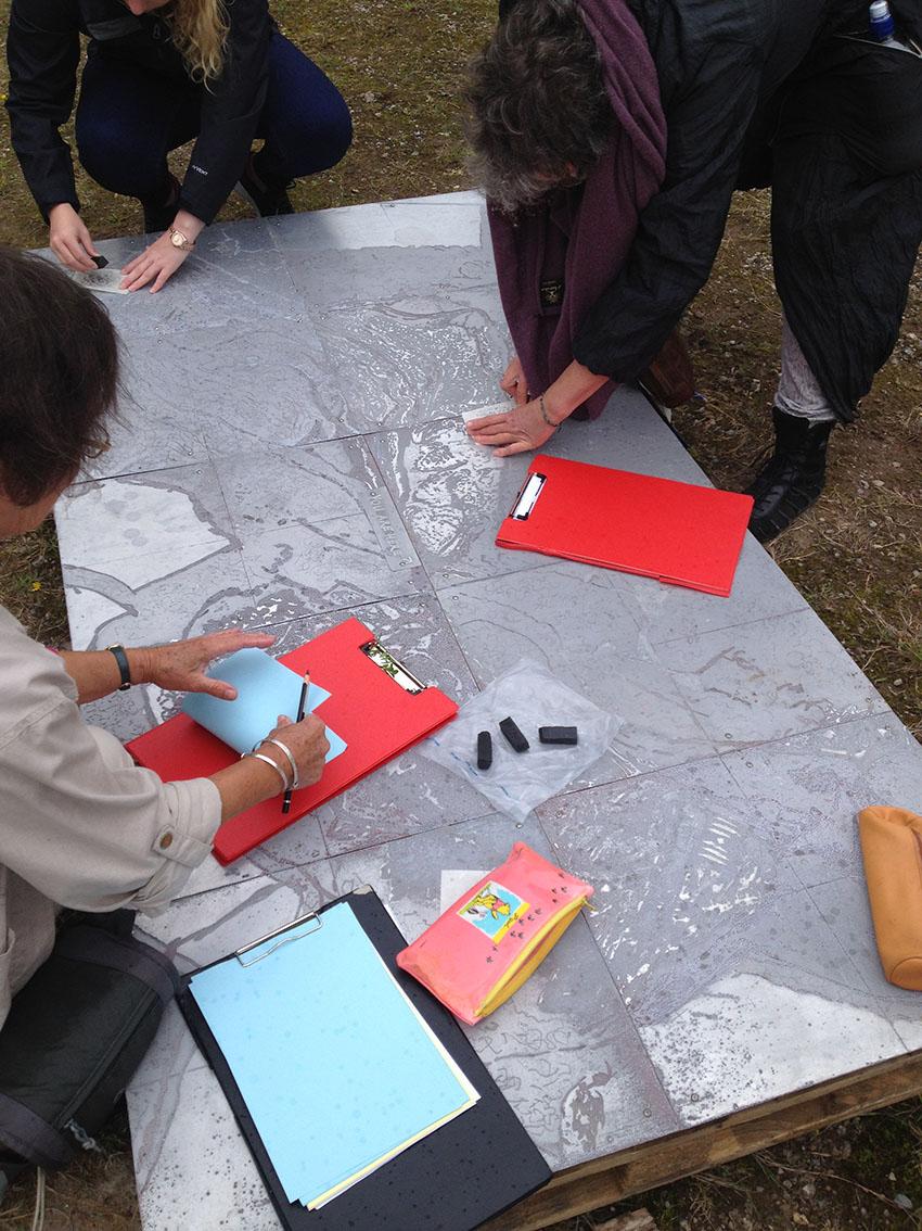 Workshop participants have a go at a rubbing